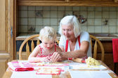 Grandmother making cookies with granddaughter — Stock Photo