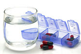 Oral medication red and black capsules in separated unit-dose box on white background. — Stock Photo