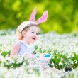 Girl wearing bunny ears playing with Easter eggs — Stock Photo #42631467
