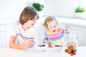 Boy and sister having fruit and cereal with strawberry for breakfast — Stock Photo