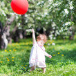 Baby girl playing with a red balloon — Stock Photo #43246107