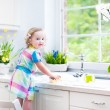 Girl washing dishes, cleaning with a sponge and playing with foam — Stock Photo