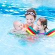 Young active mother having fun in a swimming pool with two kids — Stock Photo #43241395