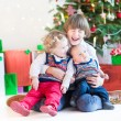 Three happy children under Christmas tree — Stock Photo