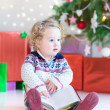 Funny little toddler girl opening her Christmas present — Stock Photo #43241555