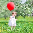 Baby girl with a big red balloon — Stock Photo