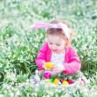 Girl playing with Easter eggs in a white basket sitting in a sunny garden — Stock Photo #43241723