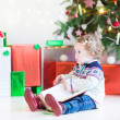 Funny little toddler girl opening her Christmas present — Stock Photo #43241787