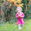 Toddler girl playing with an apple in an autumn garden — Stock Photo #43242559
