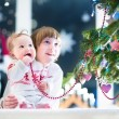 Brother and his baby sister at a Christmas tree — Stock Photo #43242599