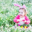 Girl playing with Easter eggs in a white basket sitting in a sunny garden — Stock Photo #43242755