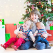 Children sitting under Christmas tree — Stock Photo