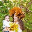 Mother holding a baby girl with a maple leaf wreath — Stock Photo #43243645