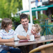 Young father enjoying a meal with his son and baby daughter — Stock Photo