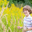 Boy playing in a yellow flower field — Stock Photo #43244203