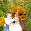 Mother holding a baby girl with a maple leaf wreath — Stock Photo #43244337