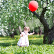 Baby girl playing with a red balloon — Stock Photo #43244499