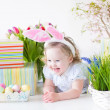 Toddler girl with bunny ears playing with Easter presents — Stock Photo #43244551