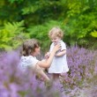 Brother and his baby sister in beautiful purple flowers — Stock Photo