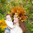 Mother holding a baby girl with a maple leaf wreath — Stock Photo