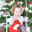 Toddler girl checking her Christmas stocking — Stock Photo