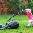 Baby girl playing with a big green lawn — Stock Photo