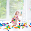 Toddler girl playing with colorful blocks — Stock Photo