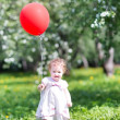 Baby girl playing with a red balloon — Stock Photo #43245603