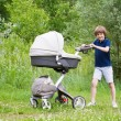 Big brother pushing a stroller — Stock Photo #43245661