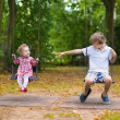 Brother and sister playing on a swing — Stock Photo #43245699