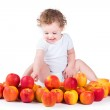 Baby girl playing with red and yellow apples — Stock Photo