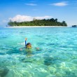 Boy snorkeling next to a tropical island — Stok fotoğraf