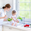 Mother and her daughter washing vegetables — Stock Photo