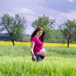 Pregnant woman walking in a summer field — Stock Photo #43246381