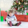 Funny little toddler girl opening her Christmas present — Stock Photo #43246481