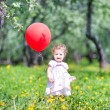 Baby girl playing with a red balloon — Stock Photo #43246703