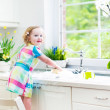 Cute curly toddler girl in a colorful dress washing dishes — Stock Photo #43246705