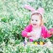 Girl playing with Easter eggs in a white basket sitting in a sunny garden — Stock Photo #43246727