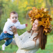 Mother holding a baby girl with a maple leaf wreath — Stock Photo #43246793