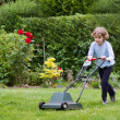 Boy playing with a lawn mower — Stock Photo #43246871