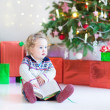 Funny little toddler girl opening her Christmas present — Stock Photo