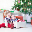 Toddler girl and her newborn brother helping to decorate a Christmas tree — Stock Photo