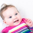 Baby girl in a knitted colorful dress — Stock Photo #43247115