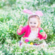 Girl playing with Easter eggs in a white basket sitting in a sunny garden — Stock Photo #43247229