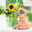 Baby girl sitting at a window next to beautiful sunflowers — Stock Photo #43247405