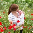 Mother and her newborn baby in a flower field — Stock Photo #43247605