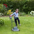 Little boy running with a lawn mower — Stock Photo #43247623