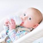 Little boy sitting in a high chair drinking milk — Stock Photo #43247653