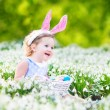 Girl wearing bunny ears playing with Easter eggs — Stock Photo #43247673