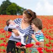 Mother with her son and newborn baby in a field — Stock Photo #43247885